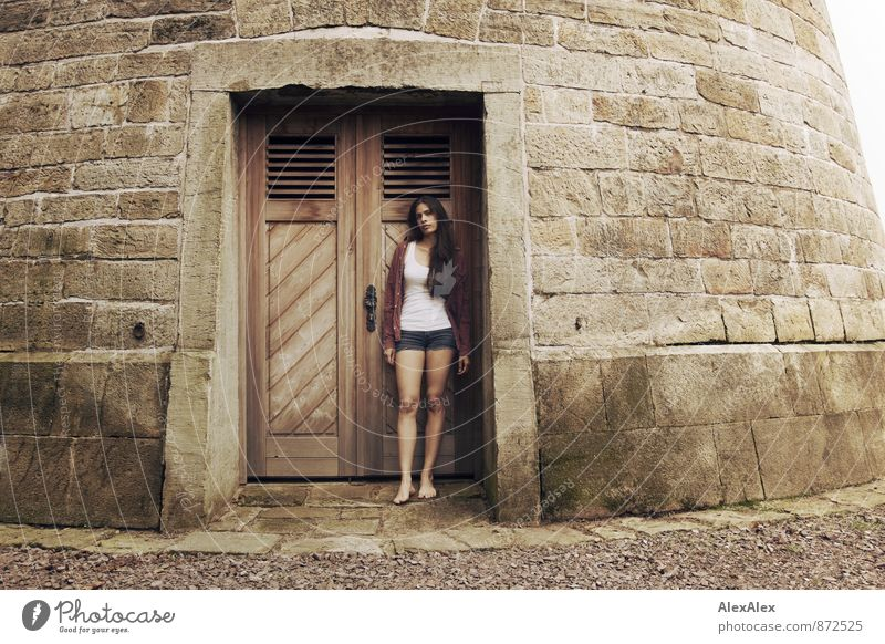 Portrait of a young woman standing in front of the wooden door of a stone tower Young woman Youth (Young adults) Barefoot 18 - 30 years Adults Castle Tower