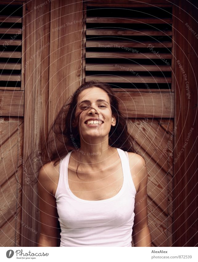 Young woman in front of a wooden door waves her long hair laughing Youth (Young adults) 18 - 30 years Adults Undershirt Black-haired Long-haired Wooden door