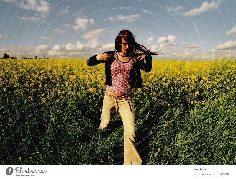 getaway Oilseed rape oil Canola Canola field Sky blue Clouds Bad weather Going Escape Flee Woman Long-haired Cardigan Flares Green Yellow Walking Summer