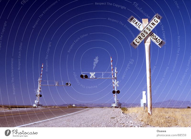 somewhere in Arizona. Steppe Control barrier Railroad tracks White Asphalt Grass Dry Traffic light Railroad crossing Transport Street sign USA Desert
