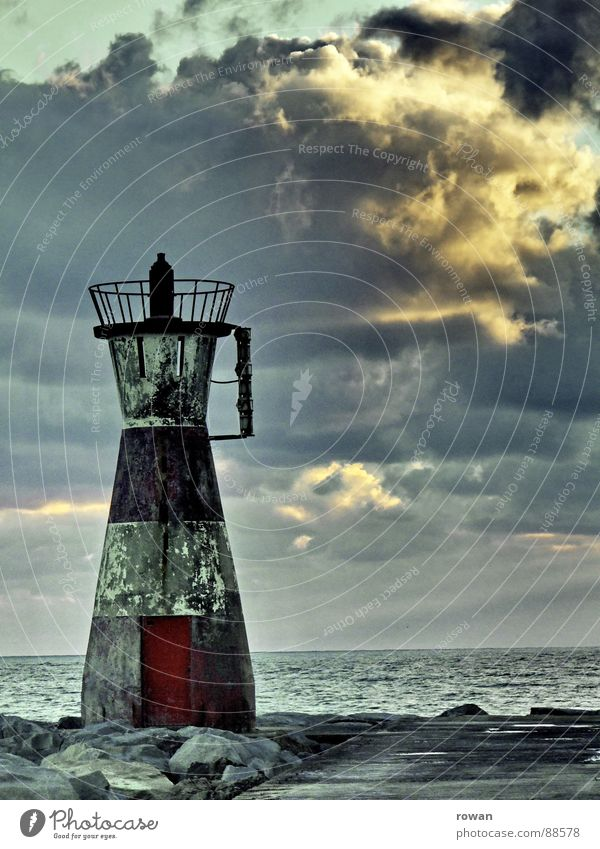 silent guard Lighthouse Red Striped Dirty Rough Ocean End Clouds Dike Jetty Sunset Calm Watercraft Navigation Safety Old Far-off places Watchfulness Indicate