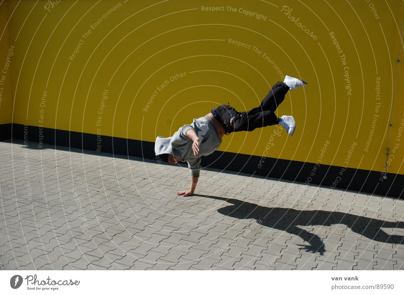 Summer Yellow Sports Wall (building) Playing Dance Asphalt Parking lot Hooded (clothing) Breakdance Shadow play Dancer Tavern