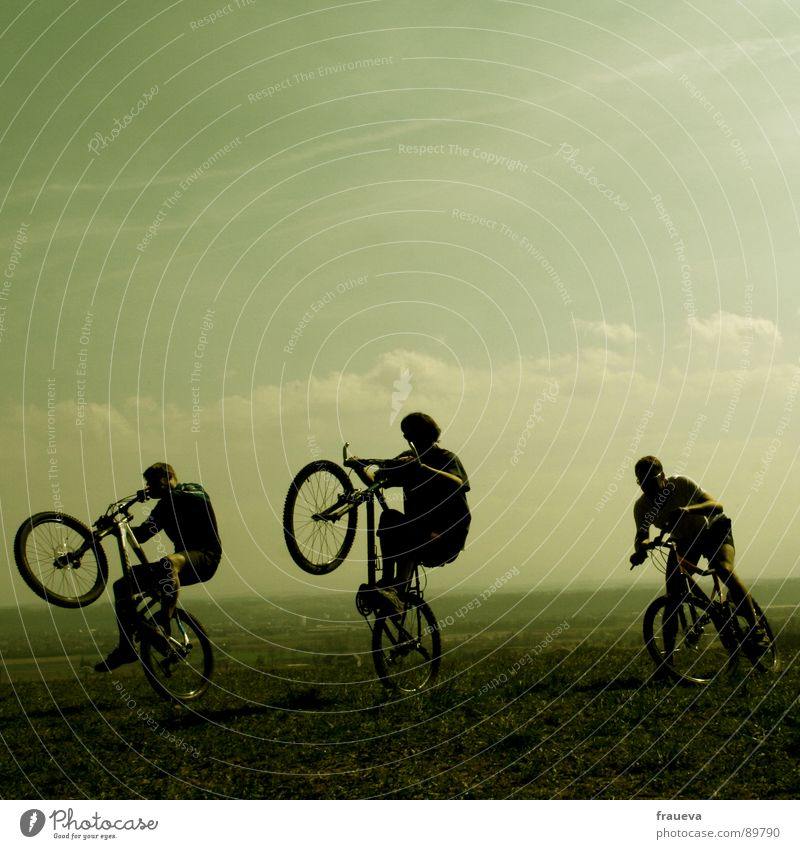 the world is a playground Cycling Bicycle Man Masculine Motorcyclist Romp Clouds Green Playing Exterior shot Happiness Exuberance Joy Group Sports willing