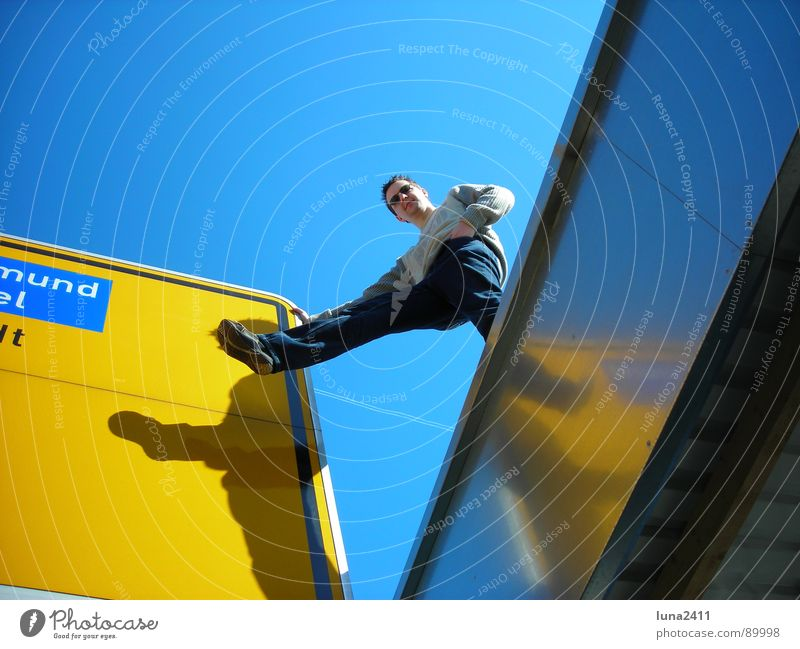 landmark ... Street sign Garage Roof Yellow Man Outstretched Easygoing Signs and labeling Road marking Signage Blue Sky Shadow Legs