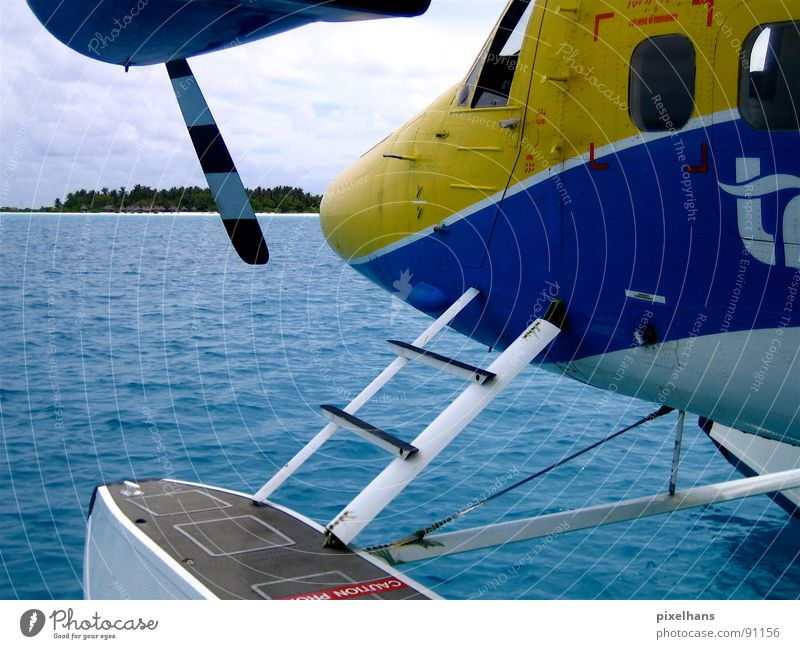 Water Ocean Blue Beach Clouds Yellow Coast Airplane Aviation Island Logistics Maldives Partially visible Section of image Indian Ocean Propeller aircraft