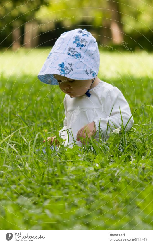 inquisitiveness Curiosity Child Baby Toddler Girl Cap Grass Meadow Sit Discover Looking Feminine Green Summer Spring Exterior shot Nature