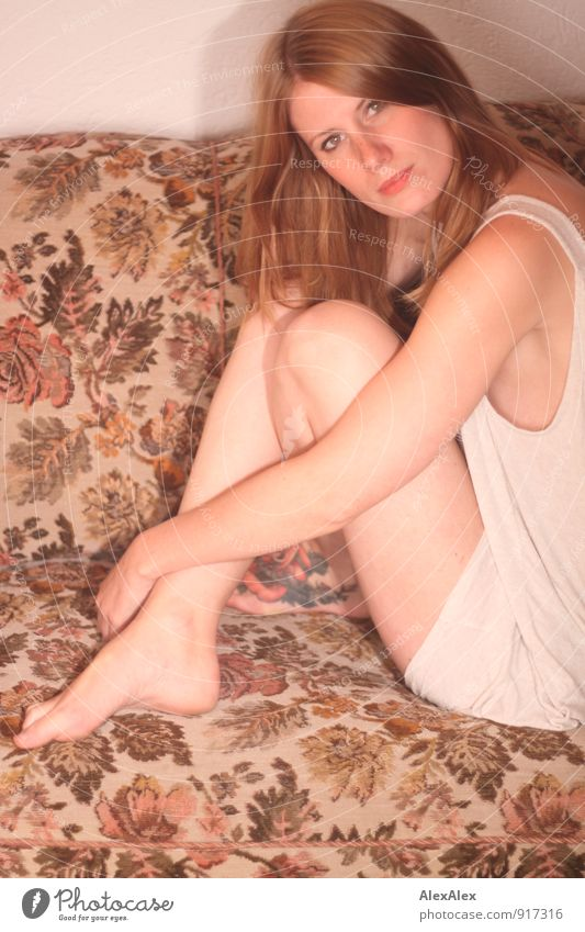 Young woman sits barefoot in undershirt on a flowered couch and looks sideways into the camera Sofa Room Youth (Young adults) Barefoot 18 - 30 years Adults