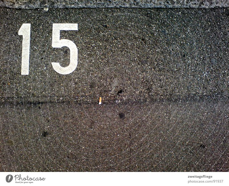 Line Floor covering Digits and numbers Asphalt Cigarette Sidewalk Traffic infrastructure Parking lot Parking Tar Chewing gum Symbols and metaphors 15 Parking space number Cigarette Butt