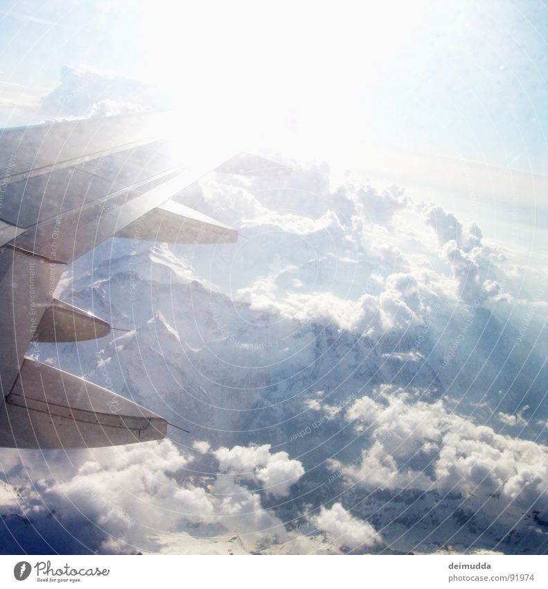 over the clouds... Airplane Clouds Glacier Volcanic crater Covers (Construction) Window Aviation Sky Sun Wing Mountain Ice Blue Tall Above Boeing steal Snow
