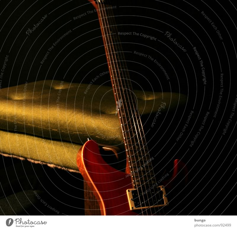 Have a seat... and play us something. Calm Loud Sound Electric guitar Musical instrument string Pick-up head Armchair Stool Bolster Pleasant Dark Light Playing