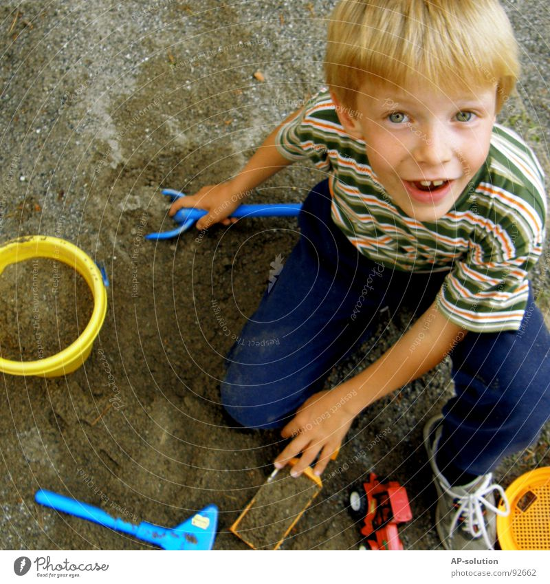 play sand Boy (child) Child Blonde Facial expression Emotions Hand Fingers T-shirt Striped Eyebrow Lips Freckles Think Small Innocent Tub Shovel Truck Tractor