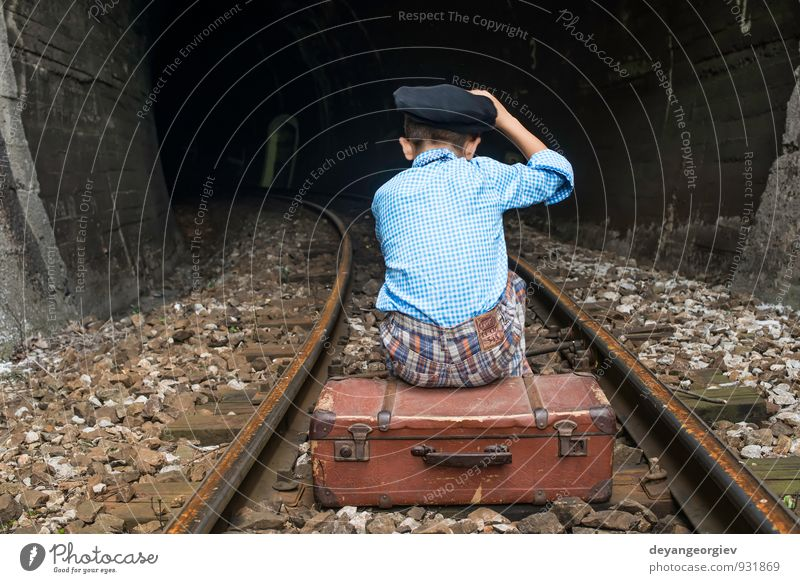 Sad young girl sitting lonely on rail track - a Royalty