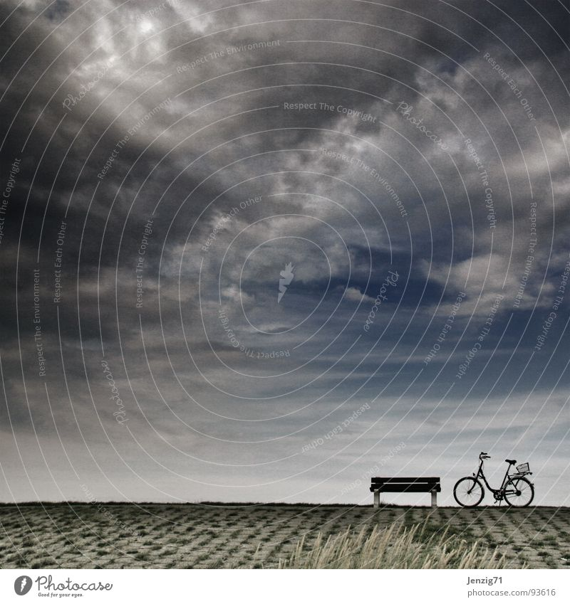 Have a seat. Dike Bicycle Break Clouds Leisure and hobbies Bench North Sea Sit biking on the bike Sky Weather