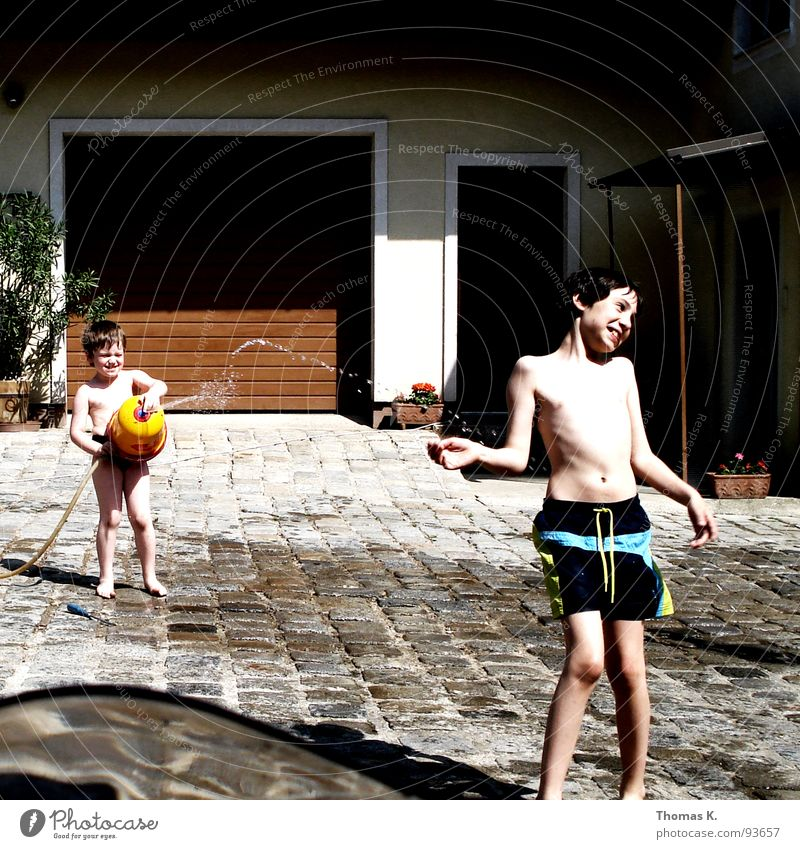 Gotcha! Child Summer Sun Vacation & Travel Garage door Cold Wet Playing Hose Swimming trunks Romp Water fountain Farm Cobblestones fresh Refreshment