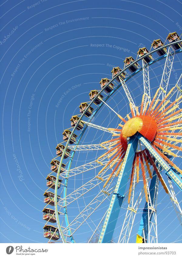 around and around Fairs & Carnivals Ferris wheel Hamburg Dom Yellow Thrill Leisure and hobbies Joy Playing Blue Orange Sky