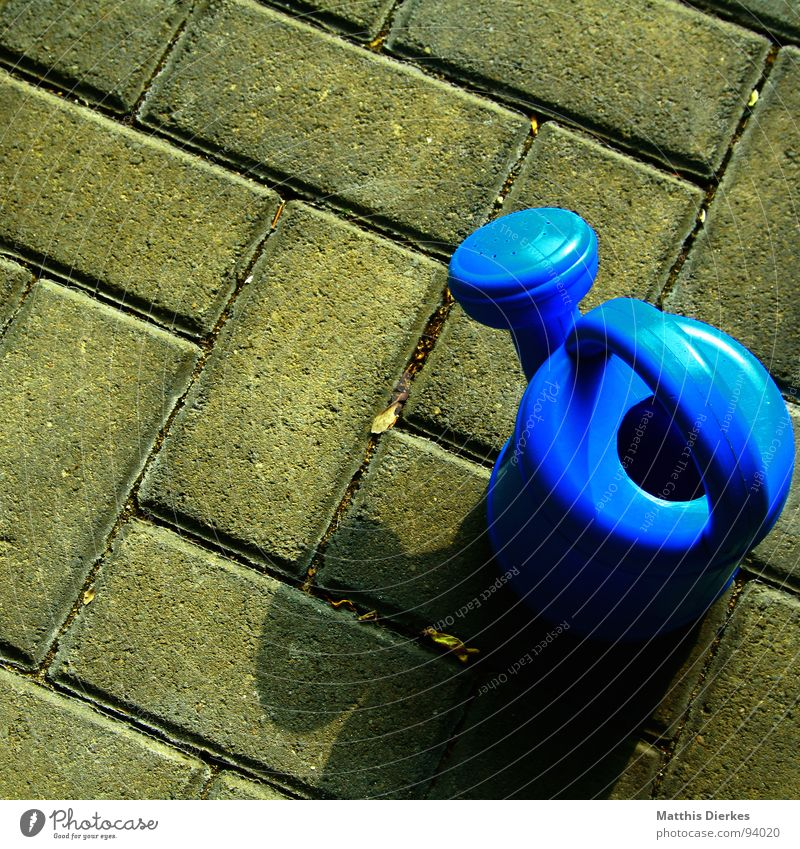 lead casting Watering can Jug Calm Carry handle Containers and vessels Blue Stone Shadow Paving stone Infancy Exterior shot Object photography Toys