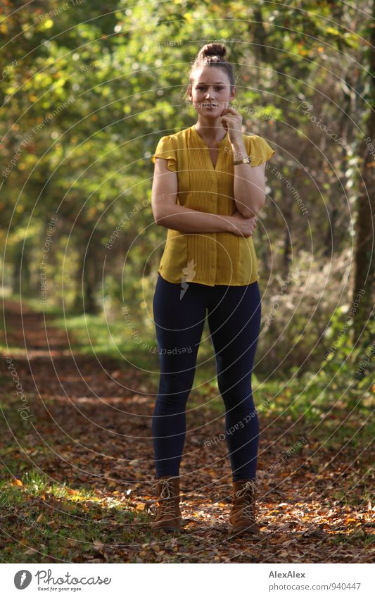 Young woman in yellow top and jeans is standing in front of a tree-lined path Trip Hiking Youth (Young adults) 18 - 30 years Adults Landscape Beautiful weather
