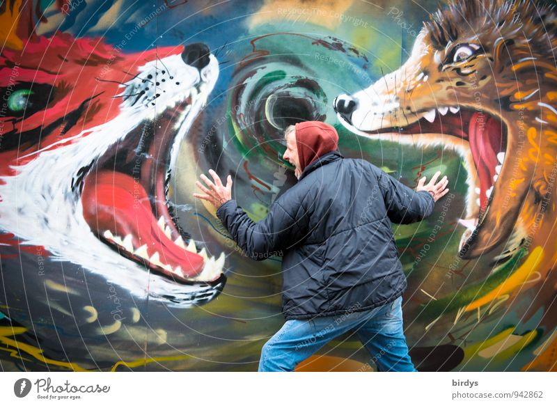 Man in hoody and jacket feels attacked by wild animals which are painted on a wall. symbolic image, nightmare Fear of death Nightmare Adults 1