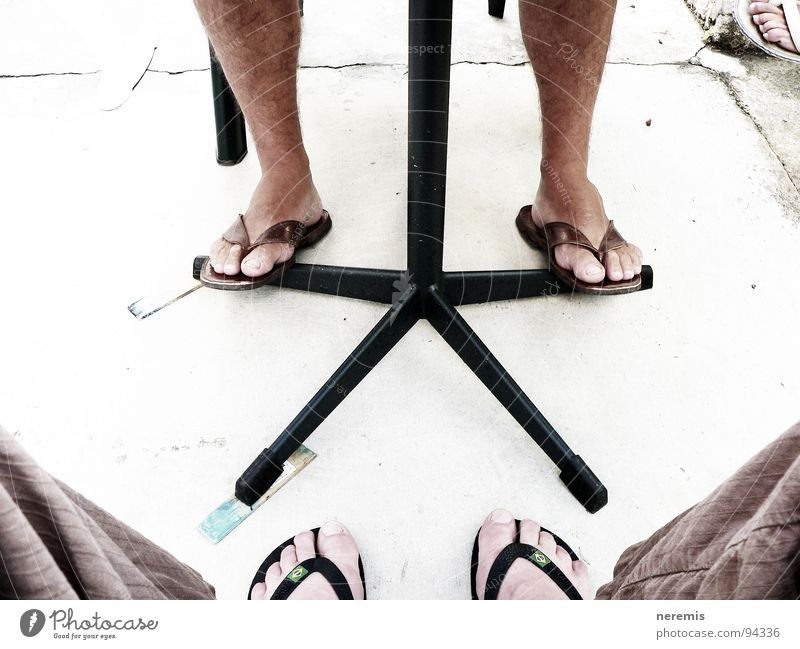 cooperation Colour photo Exterior shot Close-up Day Summer Table Man Adults Legs Feet 2 Human being Pants Flip-flops Stone Communicate Sit Firm Brown Gray White