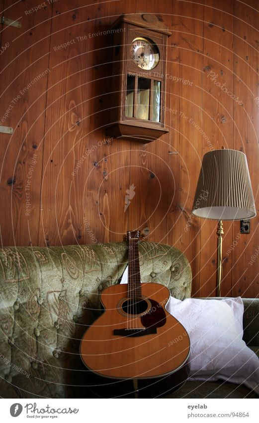 Cosiness is not a question of attitude Wall (building) Wood Wall panelling Western guitar Sofa Seating Comfortable Lamp Standard lamp Wall clock Clock Analog