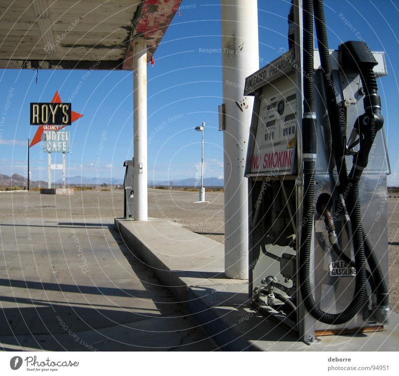 Retro American gas station on Route 66 with Roy's Motel sign in the background. Gasoline Raw materials and fuels Refuel Petrol station Americas Diesel Oil Gray