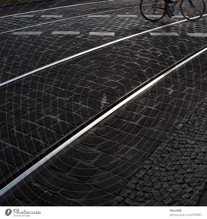 18:07 Asphalt Cobblestones Cycle path Railroad tracks Bicycle White Gray Black Home Closing time Traffic infrastructure Black & white photo Street