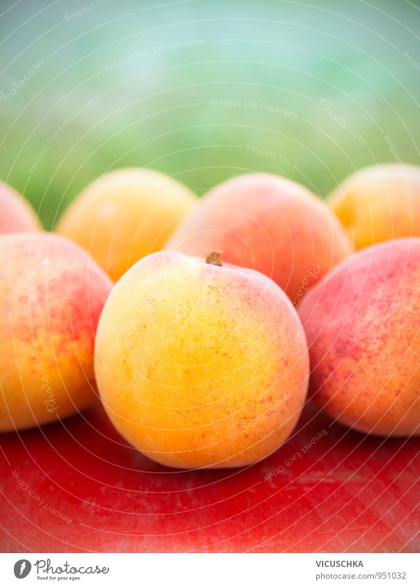 Apricots on red table in garden Food Fruit Lifestyle Healthy Eating Summer Garden Nature Yellow Green Red Table Mature Harvest Exterior shot Colour photo