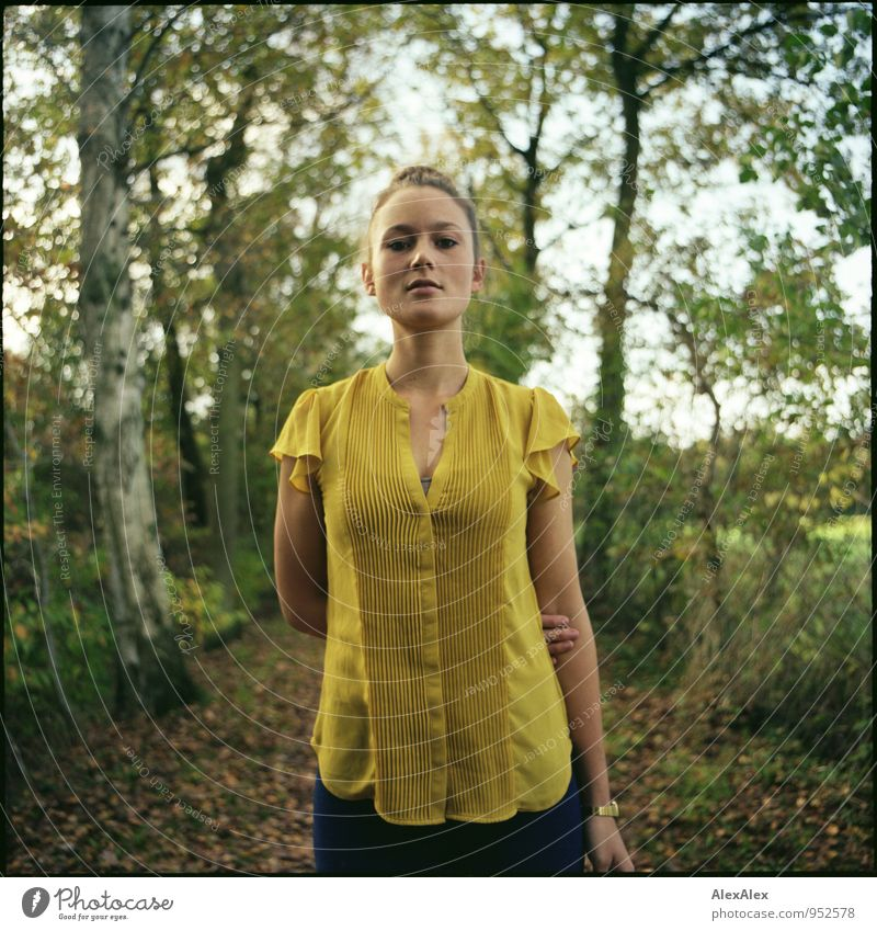 Young woman in yellow top stands in front of a tree-lined path Style Trip Adventure Youth (Young adults) 18 - 30 years Adults Beautiful weather Tree Leaf Field