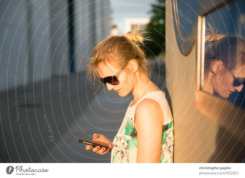Blonde woman with cell phone standing against wall Leisure and hobbies Trip City trip Cellphone PDA Human being Feminine Young woman Youth (Young adults) 1