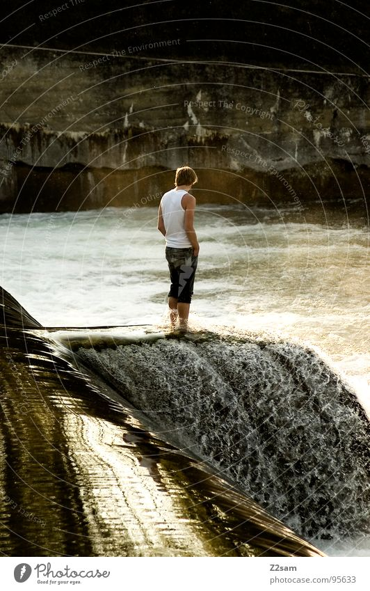 Man Youth (Young adults) Water Wall (building) Wall (barrier) Think Waves Dangerous Stand Jeans Waterfall Easygoing Surface of water White crest Current Foam