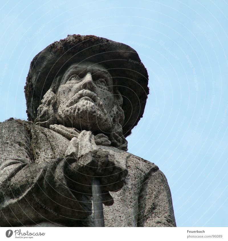 Mr. Schräg from below Colour photo Exterior shot Detail Worm's-eye view Man Adults Sculpture Sky Monument Hat Stone Blue Gray Willpower Might Disciplined