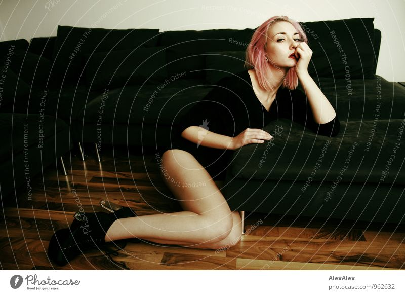 young leggy woman with pink hair sits in front of couch Living or residing Flat (apartment) Sofa Wooden floor Young woman Youth (Young adults) Face Legs
