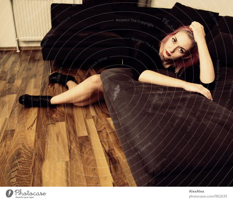 Young woman with pink hair is leaning on the couch Flat (apartment) Sofa Living room Wooden floor Night life Youth (Young adults) Legs 18 - 30 years Adults