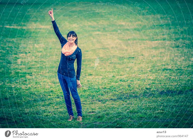 Winter ideas. Beautiful young girl stretching her finger upwards while snowing on a green meadow. pretty Human being Young woman Youth (Young adults) Woman