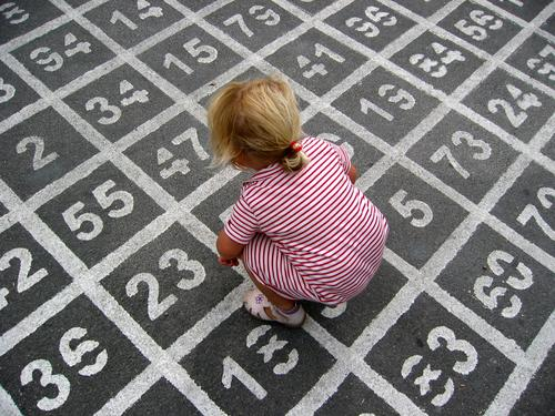 (7*5)+11-4=? Colour photo Exterior shot Day Bird's-eye view Playing Child Girl Dress Digits and numbers Crouch Infancy Asphalt Calculation Mathematics