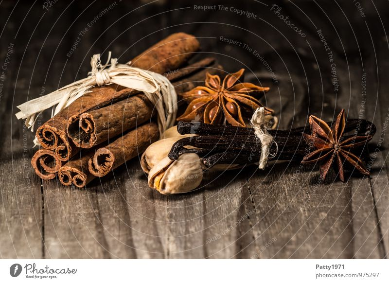 Cinnamon, aniseed, vanilla beans and nuts lie on a rustic wooden table. Christmas spices. Food Herbs and spices Vanilla pod Star aniseed Pistachio