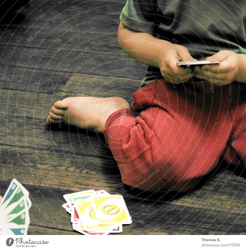 Hand Playing Wood Floor covering Pants Wooden floor Knee Fiber Game of cards