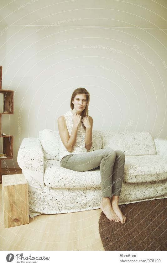 young tall woman sits on a light couch Flat (apartment) Furniture Sofa Young woman Youth (Young adults) Body Barefoot 18 - 30 years Adults Jeans Top Brunette