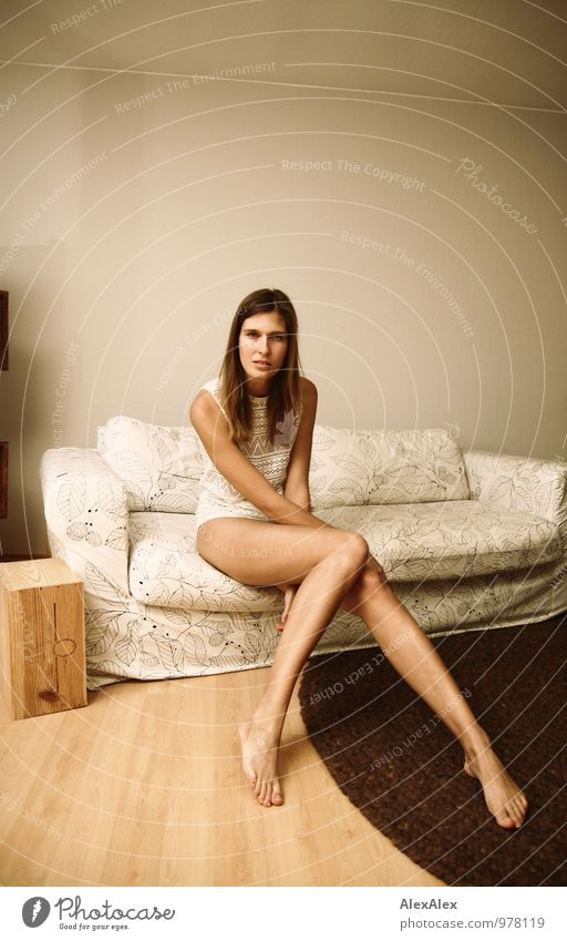 tall young leggy woman sits barefoot on light couch with bare legs Flat (apartment) Sofa Living room Young woman Youth (Young adults) Legs 18 - 30 years Adults