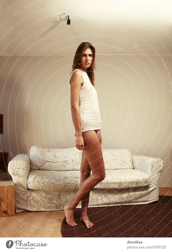 young, tall, long-legged woman stands barefoot with bare legs in front of a light sofa and looks into the camera Living or residing Flat (apartment) Sofa