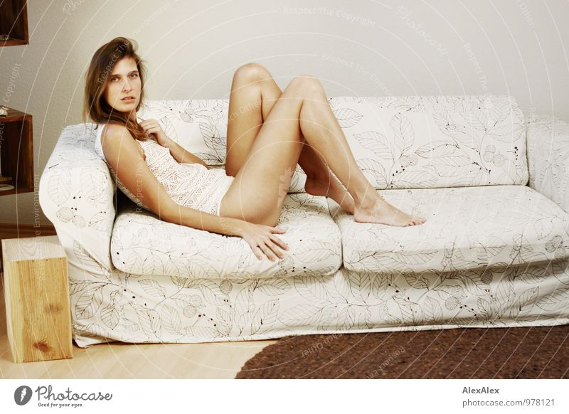 Young tall athletic woman with long bare legs sits barefoot on a light couch Flat (apartment) Sofa Living room Young woman Youth (Young adults) Legs