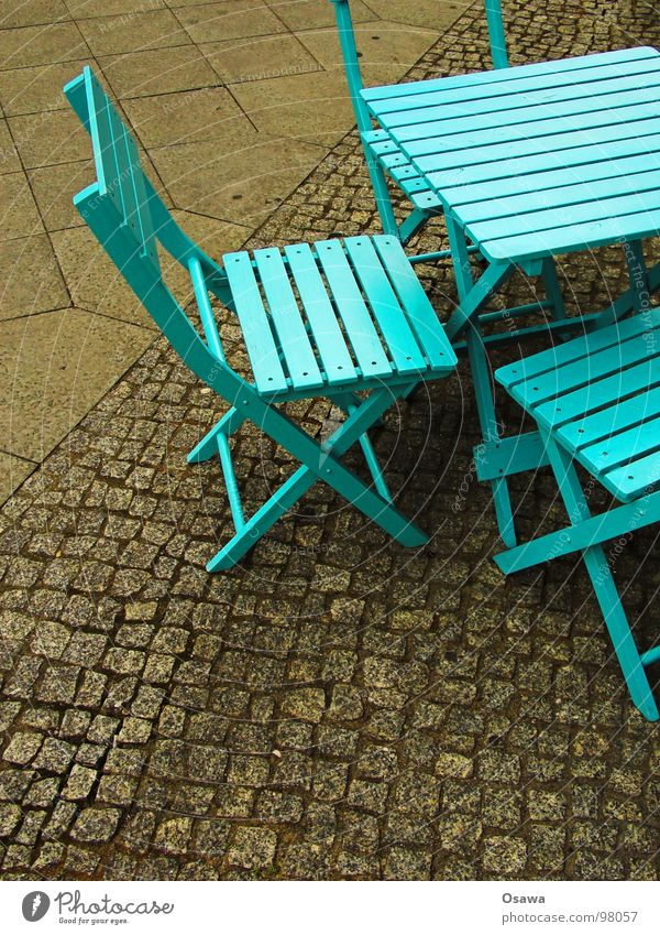 Street furniture in cyan Furniture Table Chair Wood Café Sidewalk café Cyan Green Greeny-blue Cobblestones Traffic infrastructure Camping chair Blue