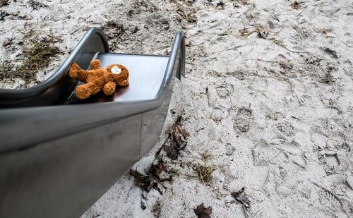 Lost / forgotten teddy bear lies on a children's slide in a playground. Playing Playground Toys Teddy bear Slide Cuddly toy Sand Metal Footprint Lie Sadness