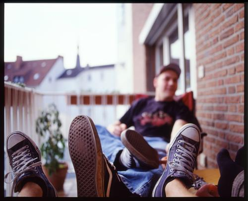 Bad manners Footwear Man Balcony Summer Beautiful weather Plant Brick Wall (building) Chucks Shoe sole Table Window Relaxation Weekend Leisure and hobbies Joy