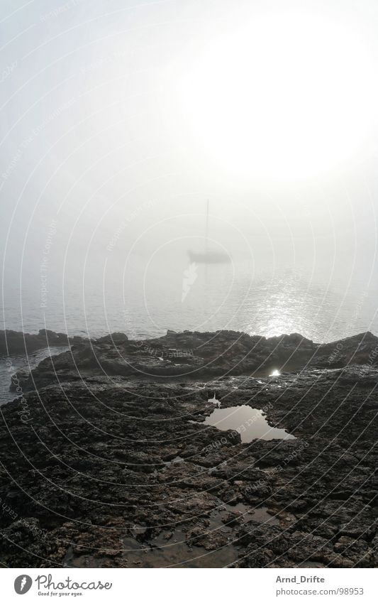 Ship in the fog Fog Ocean Watercraft Sailboat Coast Puddle Stone Morning fog Beach Sky Rock Rope