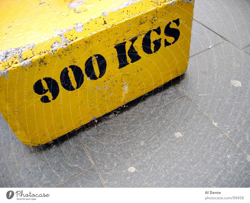 Almost a tonne Kilogram 900 Yellow Strong Town Traffic infrastructure Might Letters (alphabet) Characters kg weight heavy concrete grey gray pavement sidewalk